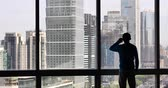 strong tea : 4k,businessman makes a phone call as overlooking the urban business building from window,skyscrapers,economic center. Stock Footage