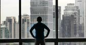 strong tea : 4K, silhouette, businessman, back, raising, arm, Overlooking, the, victory, urban, building, from,, window, skyscrapers, economic, center Stock Footage