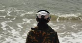billow : 4k Young man with earphones and facing the sea,enjoying the tunes in his headphones,wide ocean surface,waves washed sand,Big waves and surge.