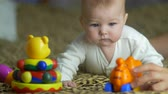 attentiveness : The baby lies on the bed look and play with toys. Close-up portrait view. Shot with Red Cinema Camera and prime telephoto lens Stock Footage