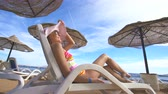 тент : The woman in a swimsuit lay on the sunbed. Wide angle