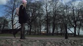 charming : Beautiful blond teen girl walking on the sidewalk around park. She is a young