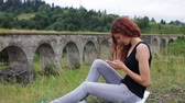 yapılı yapı : The girl writes sms sitting near the old viaduct in the mountains Stok Video