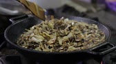 stirfry : Mushrooms are fried in a wok in the kitchen Stock Footage