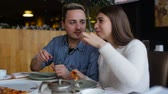 conversation : Couple talking and eating pizza in cafe in the city