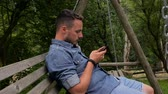 fones de ouvido : Man holding cell phone and swinging on the backyard Vídeos