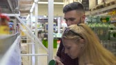 консервы : Young man and woman in supermarket choosing goods on the rack, checking them at first Стоковые видеозаписи