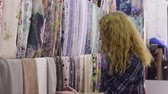 panejamento : Young beautiful woman chooses the fabric in a textile shop