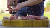 bonfile : Mens hands salt and pepper the meat. Preparing for a barbecue.