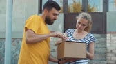 подпись : The postman delivers a parcel for a young woman