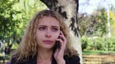 şok : girl crying speaking on the phone sitting on a bench in the park Stok Video