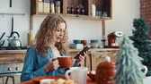 The girl drinks coffee in the morning and uses the smartphone