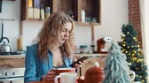 erken : Girl typing a message in the smartphone in the morning in the kitchen Stok Video