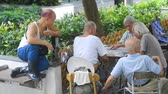 ベンチ : Hongkong, China - August 2019: Elderly people playing domino card board game sitting at table in green city park. Mature asian men having time together at desk, compete in traditional popular play on