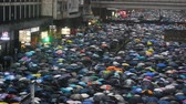 vecht : Hongkong, China - August 2019: Colorful demonstration of people with umbrellas walking along street of asian city. Crowd attends peace rally of five demands in center of Hong Kong on summer day. Top view of town and marching adults in rainy weather. Conce