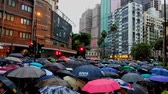 gyalogút : Hong Kong, China - August, 2019: crowded street, Anti-government protests in Hong Kong. Thousands of pro-democracy protesters walk participate in a mass rally in Hongkong. umbrella and rain