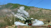 rodas : Lake Baikal, Russia - August, 2019: Old locomotive moving along railway station in countryside on autumn day. Black train runs on rail platform extruding white steam in area with mountains and houses under blue sky. Concept: tourism, railway, landscape. Stock Footage