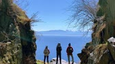 jaskinia : Lake Baikal, Russia - August, 2019: People tourists looking at sea and mountains standing on shore on sunny day. Back view of three adults enjoying natural scenery of blue cliffs and waters during baikal traveling. Concept: vacation, tourism, lifestyle. Wideo