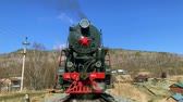 rotaie : Lake Baikal, Russia - August, 2019: Beautiful view of old locomotive and nature in countryside on fall day. Front of train emits smoke while standing on railway in area with mountains and houses under blue sky. Concept: transport, tourism, landscape.