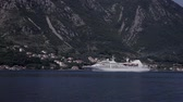 говорю : Cruise ship enters a port on a background of mountains.