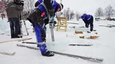 elaborate : PETROZAVODSK, RUSSIA - FEBRUARY 20, 2014: Site of International Winter Festival Hyperborea 2014 with sculptors working at ice, slider.