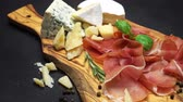 capers : sliced prosciutto and cheese on a wooden board