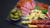 hams : Video of italian meat plate - sliced prosciutto, sausage, grissini and parmesan Stock Footage