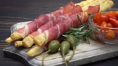 slané : italian grissini with prosciutto, capers and pepper on wooden cutting board