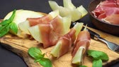 hams : sliced prosciutto and melon on a wooden board