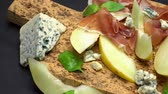 rúcula : sliced prosciutto and melon on a cork wooden board