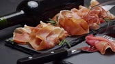 fino : sliced prosciutto or jamon meat and wine on concrete background Vídeos