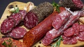 ломтики : salami and chorizo sausage close up on dark concrete background Стоковые видеозаписи