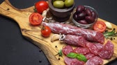 высушенный : salami and chorizo sausage close up on dark concrete background Стоковые видеозаписи
