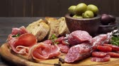 hams : sliced prosciutto and salami sausage on a wooden board