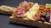 sausage slice : sliced prosciutto, cheese and salami sausage on cork wooden cutting board