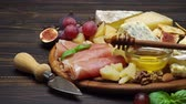 orzechy włoskie : sliced prosciutto or jamon meat and cheese on concrete background Wideo