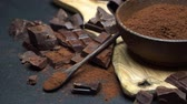 ainda : Dark Chocolate chunks and cocoa powder in wooden bowl on dark concrete background