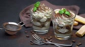 ricetta : two portions Classic tiramisu dessert in a glass on dark concrete background