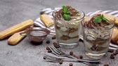 grano de cafe : two portions Classic tiramisu dessert in a glass and cup of coffee on concrete background
