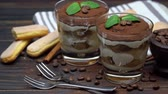 grano de cafe : two portions Classic tiramisu dessert in a glass on wooden background Archivo de Video