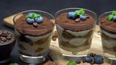 レイヤード : Classic tiramisu dessert in a glass with blueberries on dark concrete background