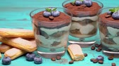 レイヤード : Classic tiramisu dessert in a glass with blueberries on blue wooden background
