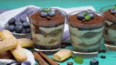 grano de cafe : Classic tiramisu dessert in a glass with blueberries on blue wooden background