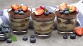 Classic tiramisu dessert with blueberries and strawberries in a glass on concrete background