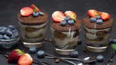 3 : Classic tiramisu dessert with blueberries and strawberries in a glass on dark concrete background 動画素材