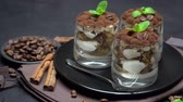 Classic tiramisu dessert in a glass on dark concrete background