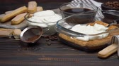 vla : talian Savoiardi ladyfingers Biscuits and cream in glass baking dish and coffee on wooden background Stockvideo