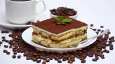 caps : Traditional Tiramisu dessert square portion and cup of fresh espresso coffee isolated on white Stock Footage