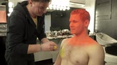 perfection : Art makeup master covering mans body with bright yellow color