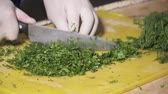 cut : CLoseup of chefs hands in gloves chopping fresh dill Stock Footage